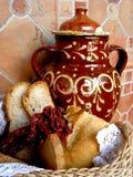 与罐、柳条筐、面包和红辣椒的静物画 库存照片
