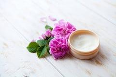 与罐的温泉概念润湿的奶油色和美丽的桃红色玫瑰 库存图片