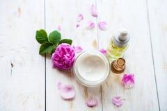 与罐的温泉概念润湿的奶油色美丽的桃红色玫瑰和玫瑰色精华在白色木背景温泉治疗上油 免版税库存照片