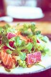与罕见的油煎的金枪鱼和三文鱼,被定调子的图象的沙拉 免版税库存照片