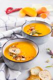 与罗斯玛丽和辣椒粉的南瓜汤 传统秋天和冬天盘 免版税库存照片