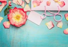 与罗莎花和瓣的桃红色苍白购物袋在蓝色绿松石破旧的别致的背景,顶视图,文本的,边界地方 图库摄影