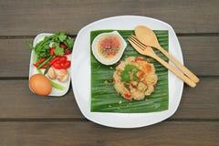 与罗非鱼油煎的服务的炒米在香蕉叶子 投入一块白色板材 库存图片