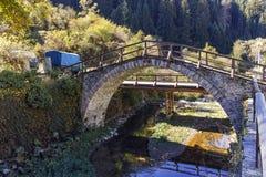 与罗马桥梁和老房子的秋天风景在Shiroka Laka,保加利亚镇  免版税库存照片
