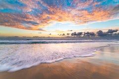 与美丽如画的日出天空的美好的海滩风景 免版税库存图片