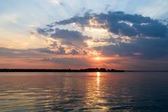 与美丽的多云天空的夏天日出在湖水 免版税库存图片