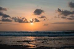 与美丽的天空的五颜六色的日落在巴厘岛的热带海滩 免版税图库摄影