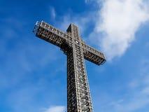 与美丽的天空蔚蓝和多云背景的金属建筑基督徒十字架 免版税图库摄影