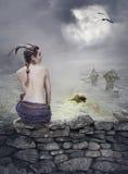 与美丽的妇女的万圣夜神秘的背景在石墙上 免版税图库摄影