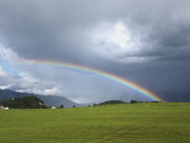 与美丽的彩虹的高山风景 山、草甸和牧场地有sunbow的 免版税库存图片