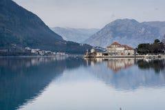 与美丽的房子和山的海风景 库存图片