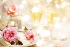 与美丽的桃红色玫瑰的饭桌 库存照片