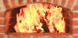 与美丽的橙色火和柴火特写镜头的壁炉作为家庭舒适和壁炉边 库存图片