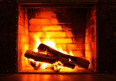 与美丽的橙色火和柴火特写镜头的家庭壁炉 库存照片