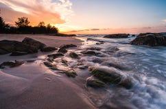 与美丽的海滩前景的橙色日落 库存照片