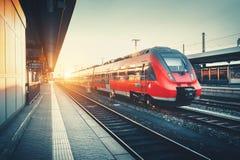与美丽的现代红色市郊火车的火车站在太阳 免版税图库摄影