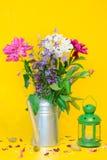 与美丽的白色和紫色牡丹花束的一幅静物画和在被弄脏的黄色背景的一个绿色灯笼 库存图片