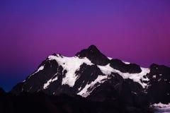 与美丽的紫色天空的审美多雪的山在背景中 库存照片