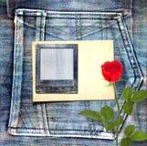 与美丽的红色玫瑰的老葡萄酒明信片在蓝色牛仔裤 免版税库存图片
