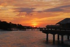 与美丽的自然天空的日落反对overwater别墅 库存照片
