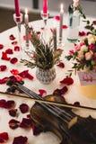 与美丽的花的浪漫桌设置在箱子,玫瑰花瓣和小提琴 库存图片