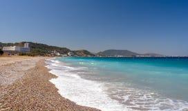 与美丽的蓝色海的小卵石海岸线罗得岛海岛的,希腊 免版税库存照片