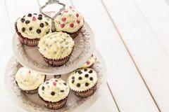 与美丽的装饰的可口情人节巧克力杯形蛋糕在轻的白色木背景,水平 图库摄影