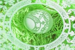 r 与美丽的阴影在一个白鸡蛋落的一个透雕细工卵形框架的一张美丽的复活节卡片 r 库存照片
