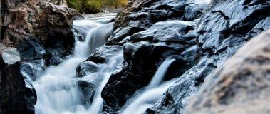 与美丽的黑石头的瀑布作用 库存图片