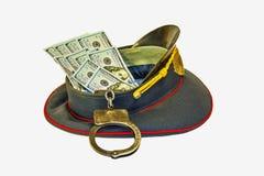 与美元和手铐的盖帽警察 免版税库存图片