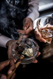 与美元钞票的商人在烟灰缸饮用的威士忌酒和抽烟的雪茄 免版税库存图片