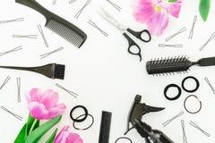 与美发师工具的框架-浪花、剪刀、梳子、发夹和郁金香在白色背景开花 平的位置,顶视图 免版税库存照片
