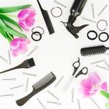 与美发师工具的秀丽框架-浪花、剪刀、梳子、发夹和郁金香在白色背景开花 平的位置,顶视图 免版税库存图片