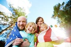 与美国国旗的可爱的家庭 库存图片