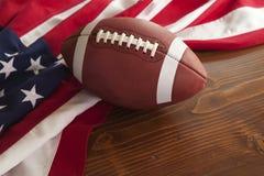 与美国国旗的橄榄球在黑暗的松木背景 免版税库存照片