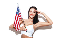 与美国旗子的性感的妇女致敬 库存照片