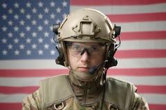 与美国旗子的年轻军人佩带的盔甲在背景 库存照片