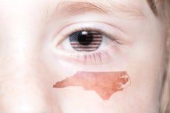 与美国的国旗的人的` s面孔和北卡罗来纳陈述地图 库存照片