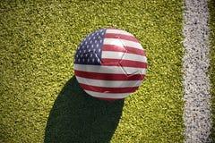 与美国的国旗的橄榄球球在领域说谎 库存图片