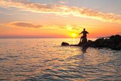 与美好的日落和年轻人渔人的海边 免版税库存照片