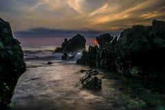 与美好的日落的黑暗的石头 库存图片