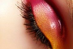 与美好的时尚明亮的构成的特写镜头女性眼睛 美丽的发光的金子,桃红色眼影膏,弄湿了闪烁 免版税库存照片