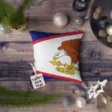 与美属萨摩亚旗子的新年快乐标记在枕头 在木桌上的圣诞装饰概念与可爱的对象 图库摄影