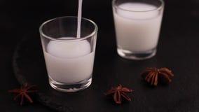 与美洲黑杜鹃的阿拉伯酒精饮料Raki在板岩黑色背景 股票录像