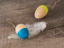 与羽毛的色的木复活节彩蛋 图库摄影