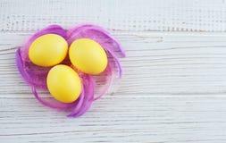 与羽毛的黄色鸡蛋在白色背景 顶视图 布加勒斯特c e办公室 免版税库存图片