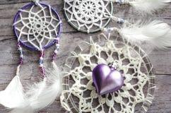 与羽毛的Dreamcatcher在木背景 种族设计, boho样式,部族标志 紫色和桃红色心脏作为V的标志 图库摄影