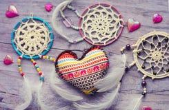与羽毛的Dreamcatcher在木背景 种族设计, boho样式,部族标志 纺织品心脏的手工制造与种族 免版税库存照片