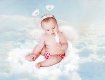 与翼和羽毛,在蓝天云彩的新出生的孩子的婴孩天使 免版税库存图片