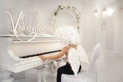 与翼的小的逗人喜爱的男婴天使,丘比特,华伦泰` s钢琴 库存图片